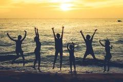 Красивый взгляд рая seascape с расплывчатыми людьми silhouette скакать на пляж в twilight времени Стоковые Фото