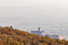 Красивый вид городка Умбрии Assisi и церков StFrancis в осени от необыкновенного места, за холмом с апельсином стоковые фото