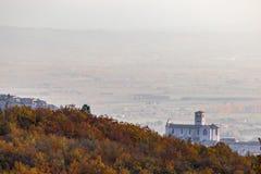 Красивый вид городка Умбрии Assisi и церков StFrancis в осени от необыкновенного места, за холмом с апельсином стоковые фотографии rf