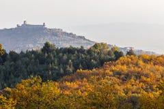 Красивый вид городка Умбрии Assisi и церков StFrancis в осени от необыкновенного места, за холмом с апельсином стоковое фото