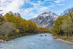 красивый вид горы с снегом и тумана с голубым рекой и стоковая фотография