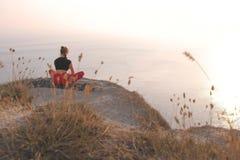Красивый вид женщины делая йогу на горе с видом на море на заходе солнца задний взгляд стоковое изображение