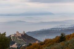 Красивый вид замка Assisi Rocca Maggior, Умбрии, Италии над морем тумана с далекими холмами на заднем плане стоковые изображения