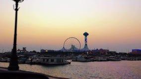 Красивый вид мола Марины и Марина наблюдают колесо на заходе солнца - пляж и шлюпки Абу-Даби сток-видео
