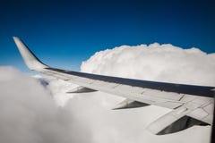 Красивый вид от иллюминатора окна Крыло самолета на предпосылке облаков и голубого неба Стоковая Фотография