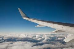 Красивый вид от иллюминатора окна Крыло самолета на предпосылке облаков и голубого неба Стоковое Изображение RF