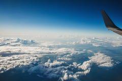 Красивый вид от иллюминатора окна крыло самолета на предпосылке облаков и голубого неба полет самолета сверх Стоковое Изображение
