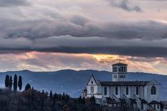 Красивый вид церков StFrancis в городке Умбрии Assisi, Италии от необыкновенного места на заходе солнца, с унылыми облаками внутр стоковое изображение rf