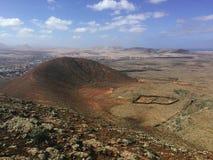 Красивый вид обозревая ржавую красную пустыню, дистантные горы в острове Фуэртевентуры, Canaries, Испании Стоковое фото RF