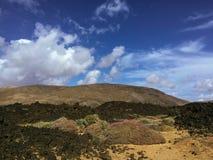 Красивый вид обозревая ржавую красную пустыню, дистантные горы в острове Фуэртевентуры, Canaries, Испании Стоковое Изображение
