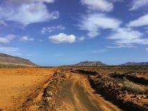 Красивый вид обозревая ржавую красную пустыню, дистантные горы в острове Фуэртевентуры, Canaries, Испании Стоковые Изображения RF
