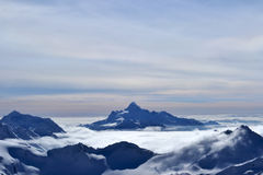Красивый вид облаков пересекая гребень горы внушительная гора Стоковое Изображение