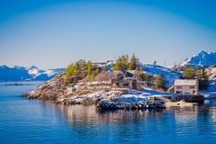 Красивый внешний взгляд деревянных зданий на утесе в взморье во время шикарного голубого неба в островах Lofoten Стоковое Изображение
