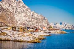 Красивый внешний взгляд деревянных зданий на утесе в взморье во время шикарного голубого неба в островах Lofoten Стоковые Фотографии RF
