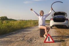 Красивый водитель девушки сидит на пустой банке для бензина рядом с сломленным автомобилем пока ждущ помощь на сельской дороге Стоковая Фотография RF