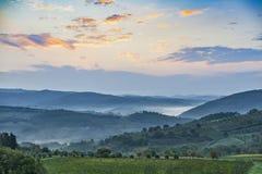 Красивый восход солнца с некоторым туманом между холмами с виноградниками Стоковые Изображения RF