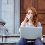 Красивый выпивать женщины устранимой чашки используя ее компьтер-книжку Стоковое Изображение RF