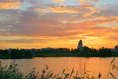 Красивый город и золотые облака захода солнца отразили в воде po Стоковая Фотография RF