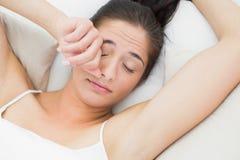 Красивый глаз затирания женщины в кровати Стоковые Фотографии RF