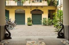 Красивый двор с аркой, заводами, парковкой для велосипедов, традиционным итальянским двором Фокус на входе стоковая фотография