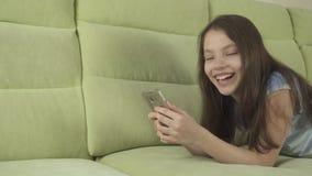 Красивый девочка-подросток имея потеху связывая на видео отснятого видеоматериала запаса smartphone видеоматериал