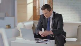 Красивый деловой костюм человека заканчивает телефонный звонок, работает на компьтер-книжке акции видеоматериалы