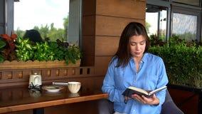 Красивый дневник чтения девушки на кафе Стоковое Изображение RF