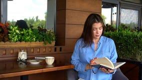 Красивый дневник чтения девушки на кафе Стоковые Изображения