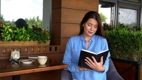 Красивый дневник чтения девушки на кафе Стоковая Фотография