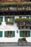 Красивый домашний фасад с деревянными окнами и цветками Стоковое Фото