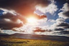 Красивый драматический заход солнца в горах Ландшафт при свет солнца светя через облака Стоковые Изображения