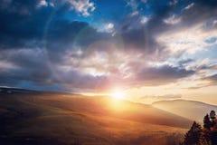 Красивый драматический заход солнца в горах Ландшафт при свет солнца светя через облака Стоковое Изображение