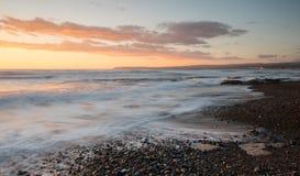 Красивый драматический заход солнца над скалистым побережьем стоковые изображения
