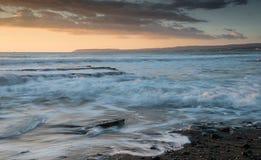 Красивый драматический заход солнца над скалистым побережьем стоковые изображения rf