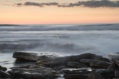 Красивый драматический заход солнца над скалистым побережьем стоковое фото rf
