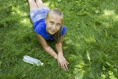 Красивый девочка-подросток в парке лежа на зеленой траве Стоковые Фотографии RF