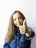 Красивый девочка-подросток показывая tumbs вверх в рубашке джинсов Стоковые Фотографии RF