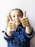 Красивый девочка-подросток показывая tumbs вверх в рубашке джинсов Стоковое Фото