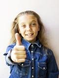 Красивый девочка-подросток показывая tumbs вверх в рубашке джинсов Стоковые Изображения
