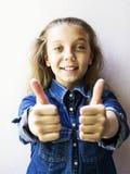 Красивый девочка-подросток показывая tumbs вверх в рубашке джинсов Стоковые Фото