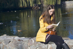 Красивый девушк-студент сидит на парапете около пруда города в солнце Стоковое Фото