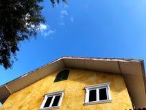 Красивый желтый дом с ясными голубого листьями неба и зеленого цвета Стоковое Изображение