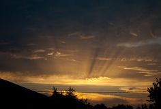 Красивый желтый заход солнца, лучи заходящего солнца, облака в небе вечера Стоковое фото RF