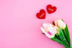 Красивый желтых цветка тюльпана и подушки формы сердца с плоским положением на розовой предпосылке Стоковое Изображение RF