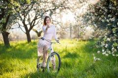 Красивый женский велосипедист с ретро садом велосипеда весной Стоковое Изображение