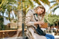 Красивый женский говорить на мобильном телефоне, ища в тетради стоковые фотографии rf