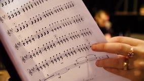 Красивый женский композитор музыки смотря примечания музыки Женщина смотрит примечания на крупном плане рояля сток-видео