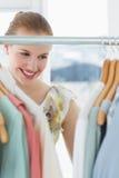 Красивый женский клиент выбирая одежды на магазине Стоковое фото RF
