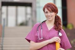 Красивый женский медицинский профессионал внутри scrubs снаружи стоковая фотография rf