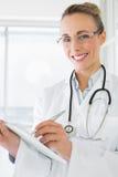 Красивый женский доктор с доской сзажимом для бумаги в больнице Стоковая Фотография RF
